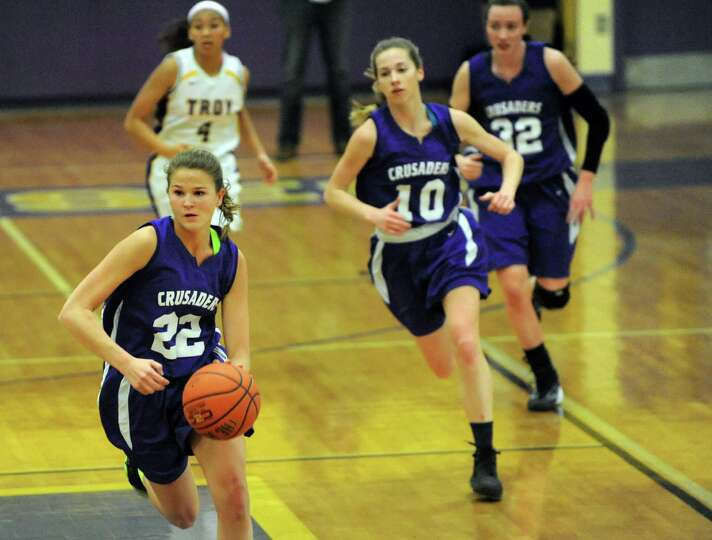 Catholic Central's Madison Purcell, left, drives the ball up court during their basketball game agai
