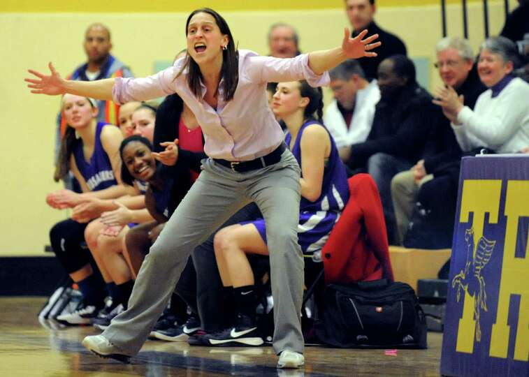 Catholic Central's coach Audra DiBacco, center, cheers on her team during their basketball game agai