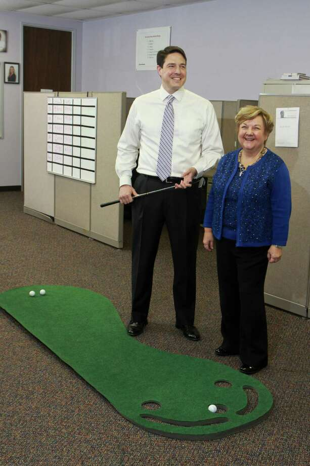 (For the Chronicle/Gary Fountain, January 27, 2014) Jeff Corte and D'Lea Nichols of Unishippers, using the putting green in the sales office. Photo: Gary Fountain, Freelance / Copyright 2014 Gary Fountain.