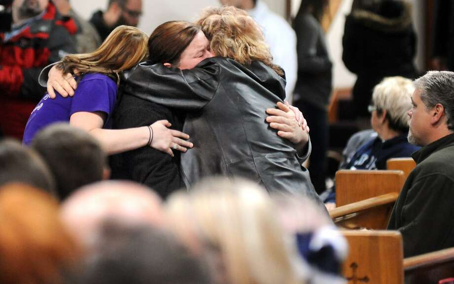 Family members of Chad and LaRae Watson including Linda Robertson, center, Kristen Robertson, 19, left, and Sandi Moore hug before the memorial service Friday Jan. 31, 2014,  at Calvary Missionary Baptist Church in Central City. LaRae Watson and eight of the couples nine children died in a fire Thursday at their Depoy home. Chad Watson and Kylie Watson, 11, are in Nashville at Vanderbilt University Medical Center and Monroe Carrell Children's Hospital, respectively, at Vanderbilt.    (AP Photo/Messenger-Inquirer, Jenny Sevcik) Photo: Jenny Sevcik, Associated Press
