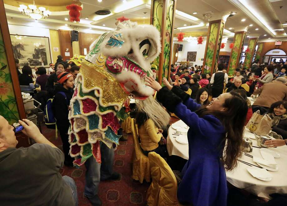 A lion dancer, from the New York Rockits A.I.A., circulates in Grand Harmony Restaurant, in New York's Chinatown, Friday, Jan. 31, 2014. The Lunar New Year this year marks the Year of the Horse on the Chinese calendar. (AP Photo/Richard Drew) Photo: Richard Drew, Associated Press