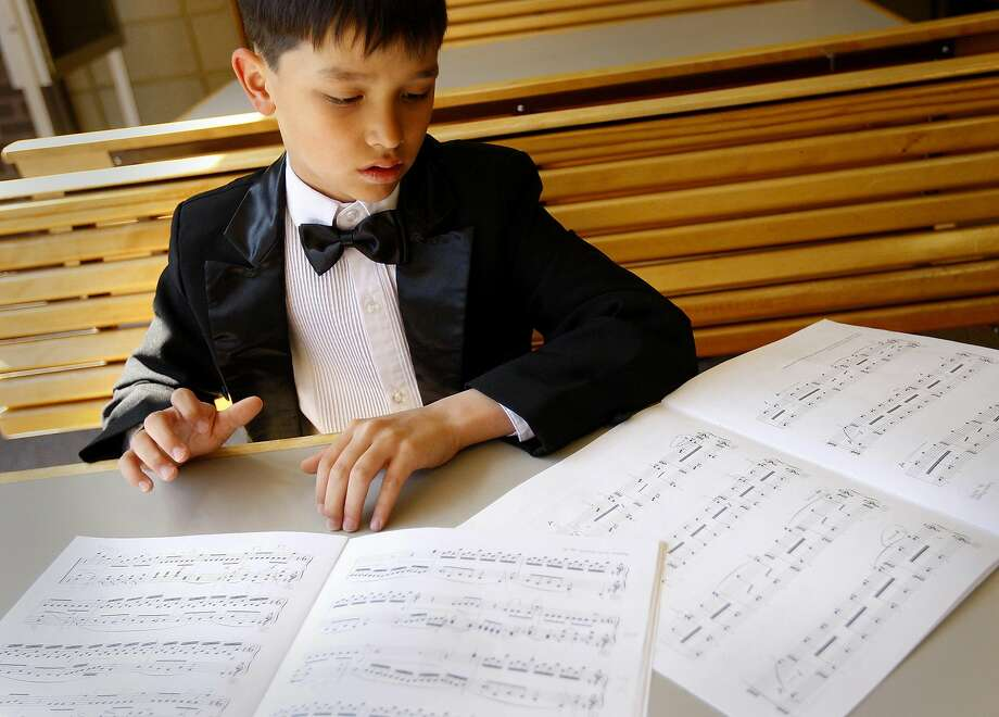 In this April 28, 2012 photo, James Wilson looks over a score while miming the music with his hands shortly before a recital in Laramie, Wyo. Wilson, 12, has been playing the piano since age 3 and will perform Friday, Jan. 31, 2014, at the Lagny-sur-Marne International Piano Competition outside Paris. The Casper Star-Tribune reports that Wilson is one of just two Americans playing in the competition. (AP Photo/Casper Star-Tribune, Dan Cepeda, File) Photo: Dan Cepeda, Associated Press