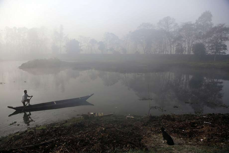An Indian man rows a boat on a foggy morning on the outskirts of Gauhati, India, Friday, Jan. 31, 2014. Though India is famous for its brutally hot summers, temperatures fall sharply for a few weeks in December and January, badly affecting means of communication as visibility suffers due to heavy fog, and leads to deaths of poor people who are forced to spend nights away from the warm comforts of homes. (AP Photo/Anupam Nath) Photo: Anupam Nath, Associated Press