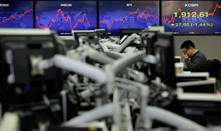 A currency trader watches the Korea Composite Stock Price Index at the foreign exchange dealing room of the Korea Exchange Bank headquarters in Seoul. Photo: Lee Jin-man, STF / AP