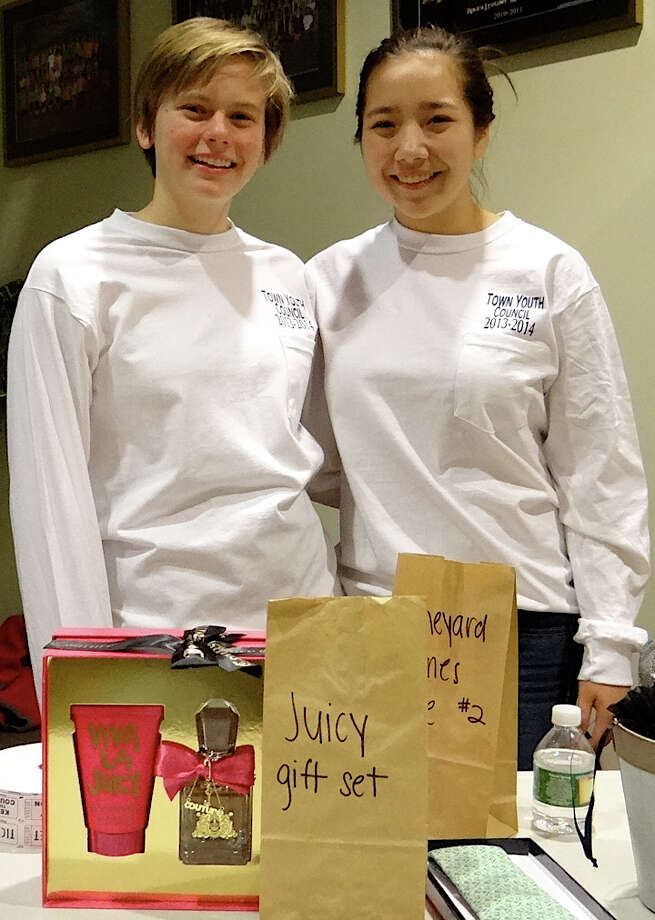 Town Youth Council members Riley Blumenfield, 15, and Mia Jensen, 16, with raffle items at the concert to benefit Typhoon Haiyan relief programs at Roger Ludlowe Middle School on Friday evening. Photo: Mike Lauterborn / Fairfield Citizen contributed