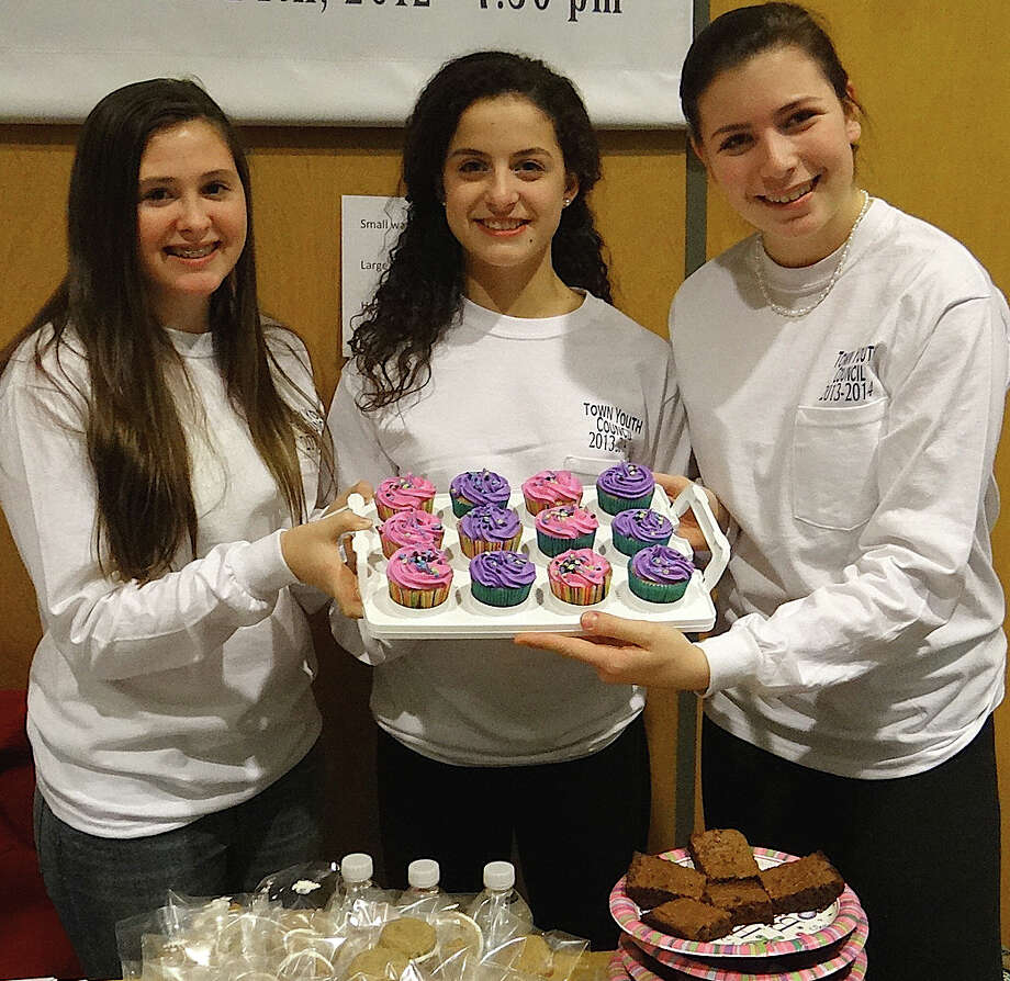 Town Youth Council members Carolyn Tangney, 16; Anna Katz, 14, and Samantha Strelzer, 15, with baked goods sold to benefit typhoon relieft efforts at the Friday night concert organized by the council at Roger Ludlowe Middle School. Photo: Mike Lauterborn / Fairfield Citizen contributed