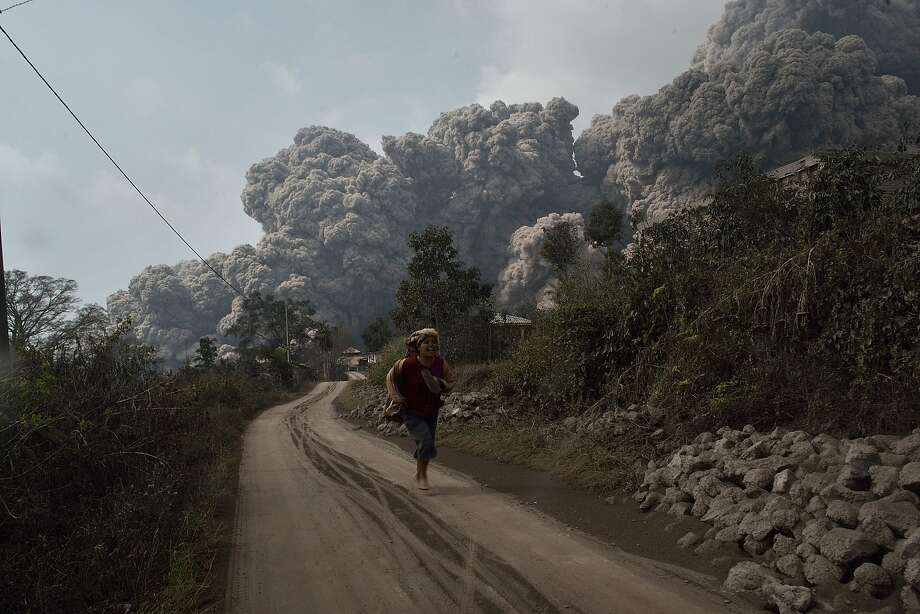 Deadly cloud: A villager runs to escape from a cloud of hot volcanic ash engulfing villages in Karo district 