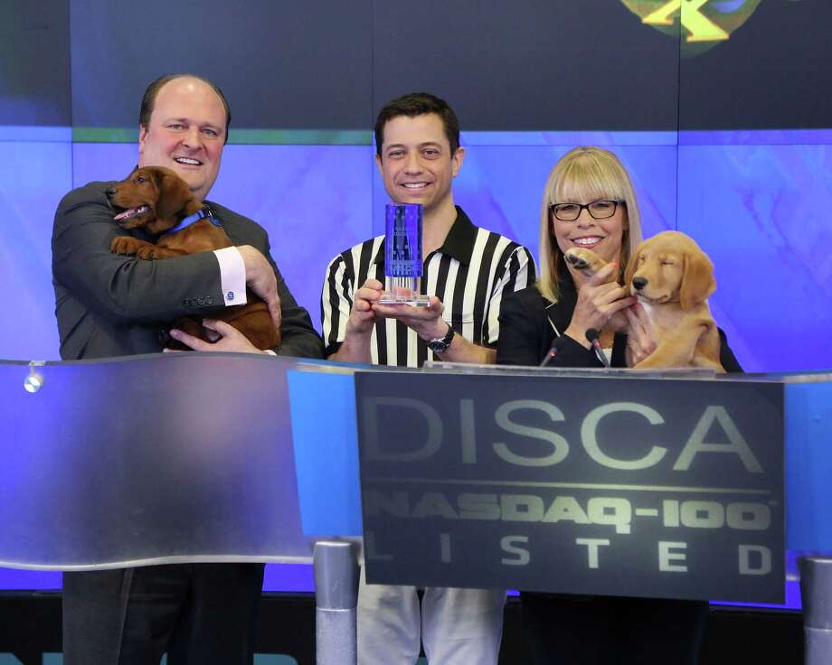 NEW YORK, NY - JANUARY 31:  An executive, Puppy Bowl referee Dan Schachner, and Group President, Animal Planet, Science, and Velocity Marjorie Kaplan ring the closing bell in honor of Puppy Bowl at NASDAQ MarketSite on January 31, 2014 in New York City. Photo: Taylor Hill, Getty Images / 2014 Getty Images