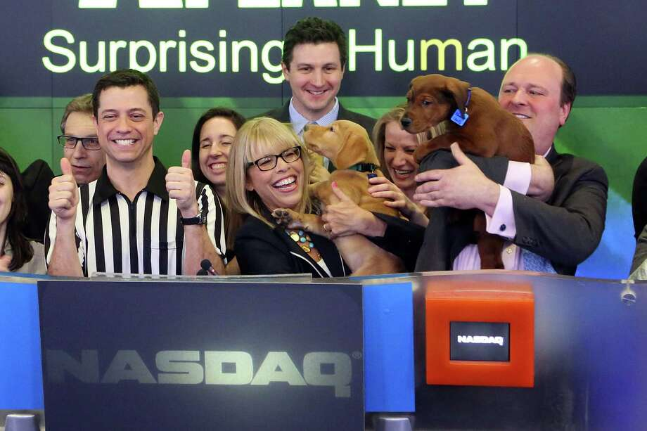NEW YORK, NY - JANUARY 31:  Puppy Bowl referee Dan Schachner, Group President for Animal Planet, Science, and Velocity Marjorie Kaplan, and puppies ring the closing bell at NASDAQ MarketSite on January 31, 2014 in New York City. Photo: Taylor Hill, Getty Images / 2014 Getty Images