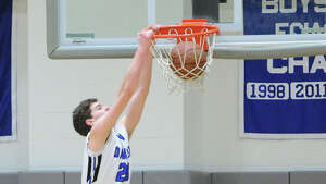 At left, George Phillips of Darien dunks the ball on Tommy Povinelli of  Greenwich during the boys high school basketball game between Darien  High School and Greenwich High School at Darien, Friday night, Jan. 31,  2014.