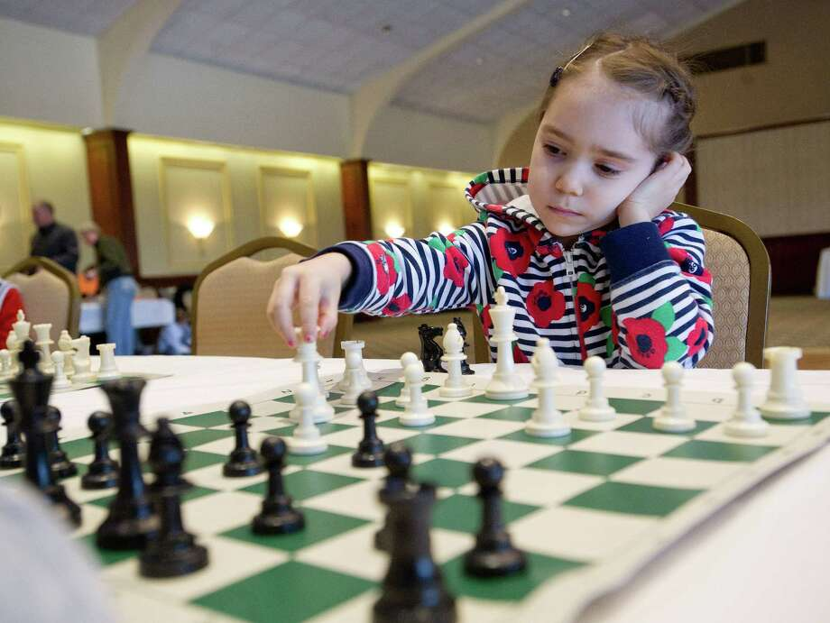 Diana Balkovski plays a chess match against Rogan Rocket Lowe during the National Educational Chess Association's tournament at the Italian Center in Stamford, Conn., on Saturday, February 1, 2014. Photo: Lindsay Perry / Stamford Advocate