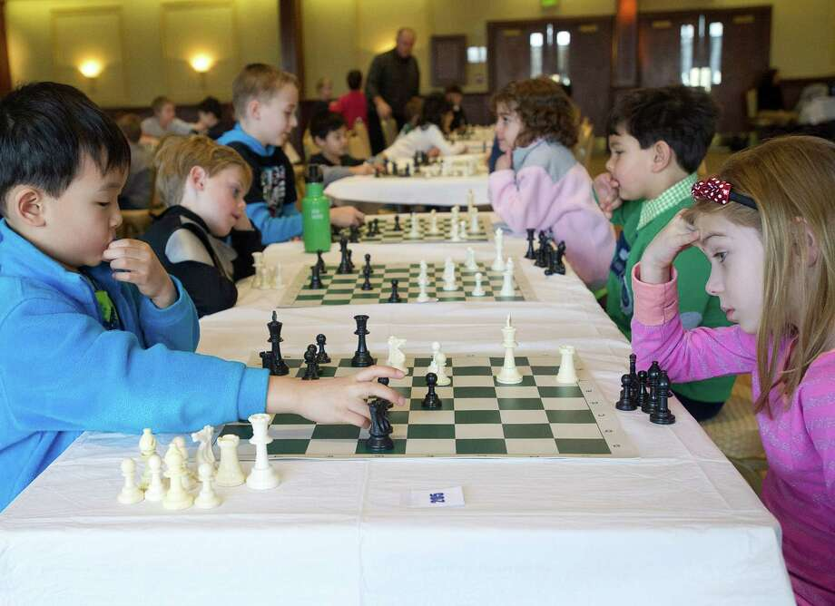 Kids, including Luyao Zachary Guo, left, and Delphine Brown, right, play chess games during the National Educational Chess Association's tournament at the Italian Center in Stamford, Conn., on Saturday, February 1, 2014. Photo: Lindsay Perry / Stamford Advocate