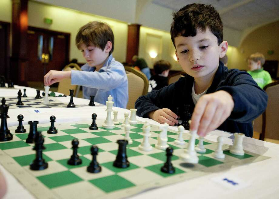 Jack Saucedo, right, plays a match against Aidan Aybar during the National Educational Chess Association's tournament at the Italian Center in Stamford, Conn., on Saturday, February 1, 2014. Photo: Lindsay Perry / Stamford Advocate