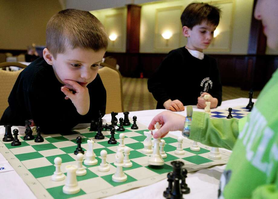 Bark Homan, left, plays a chess match against William Knispel during the National Educational Chess Association's tournament at the Italian Center in Stamford, Conn., on Saturday, February 1, 2014. Photo: Lindsay Perry / Stamford Advocate