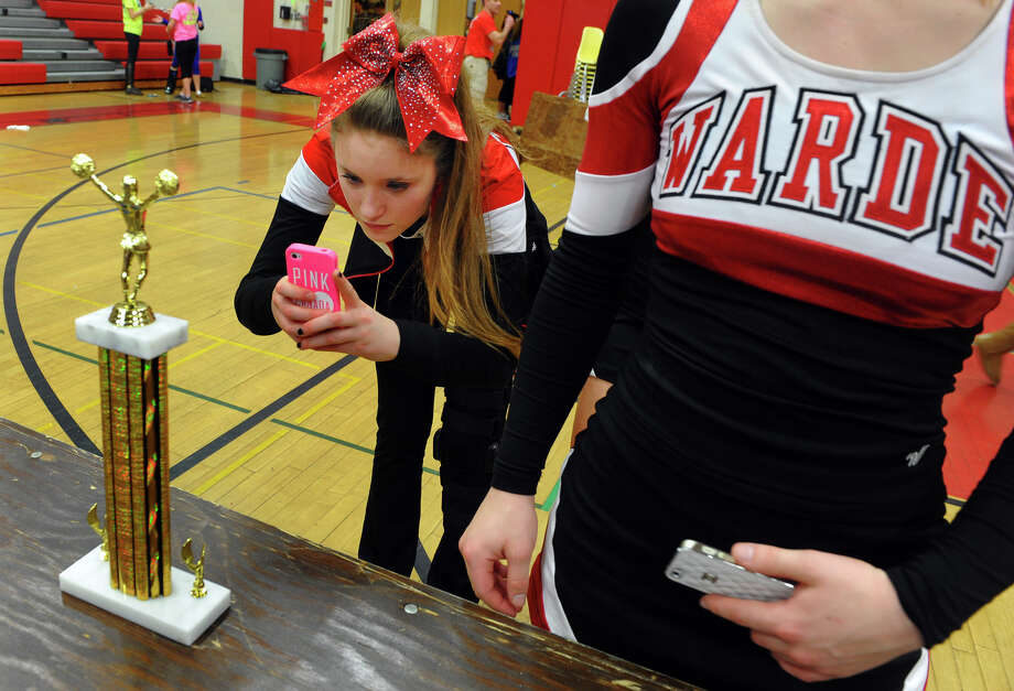 Fairfield Warde's Bella Miserocchi snaps a photo of the team's 1st place trophy at the end of the 17th Annual 2014 FCIAC Cheerleading Competition at Fairfield Warde High School in Fairfield, Conn. on Saturday February 1, 2014. Photo: Christian Abraham / Connecticut Post