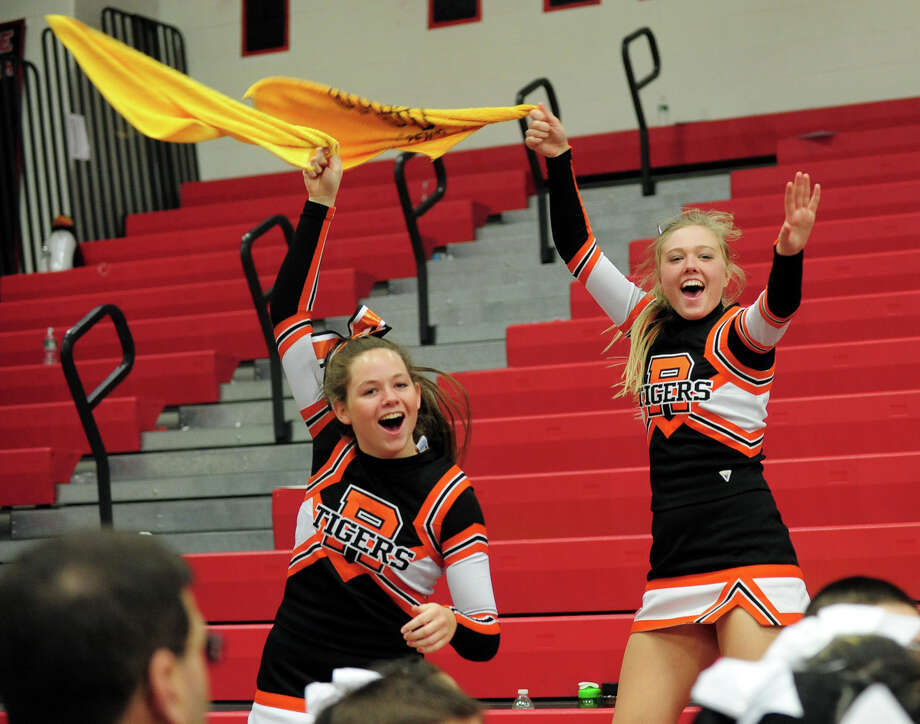 Ridgefield's Kristin NcKeown and teammate Courtney Herrington, right, wave towels at the finish of the 17th Annual 2014 FCIAC Cheerleading Competition at Fairfield Warde High School in Fairfield, Conn. on Saturday February 1, 2014. Photo: Christian Abraham / Connecticut Post