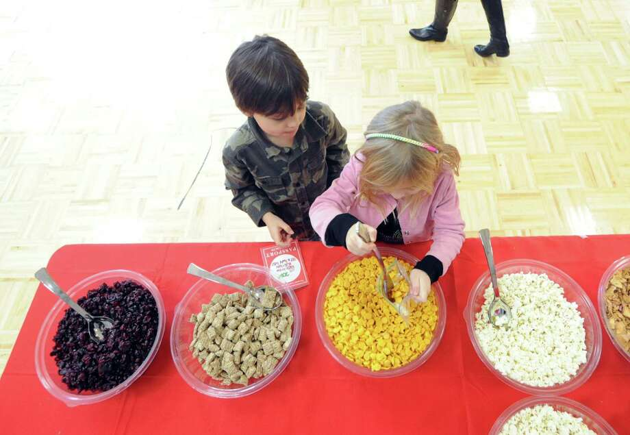 From left, brother and sister, Sebastian and Andrea Cordulack, 8 and 6, sample organic trail mix during the Kids in the Kitchen Fit & Fun Fest at the YWCA of Greenwich, Saturday afternoon, Feb. 1, 2014. The event was sponsored by the Junior League of Greenwich to promote children's health. Photo: Bob Luckey / Greenwich Time