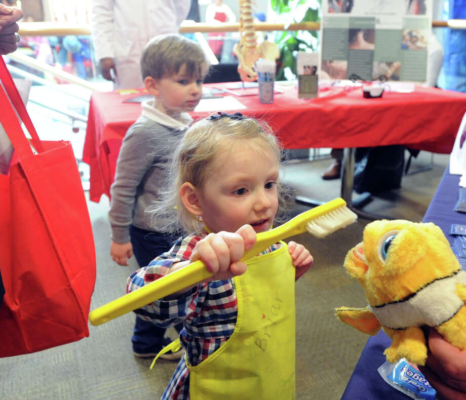 Briar Lissauer, 3, of Greenwich, learns how to properly use a toothbrush by brushing a puppet's teeth at the Harbor Point Dental Group of Stamford booth during the Kids in the Kitchen Fit & Fun Fest at the YWCA of Greenwich, Saturday afternoon, Feb. 1, 2014. The event was sponsored by the Junior League of Greenwich to promote children's health. Photo: Bob Luckey / Greenwich Time