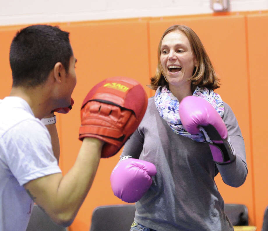At right, Jen Byxbee of Stamford, learns kickboxing from Arnold Baterna of Punch Fitness Center of Greenwich during the Kids in the Kitchen Fit & Fun Fest at the YWCA of Greenwich, Saturday afternoon, Feb. 1, 2014. The event was sponsored by the Junior League of Greenwich to promote children's health. Photo: Bob Luckey / Greenwich Time