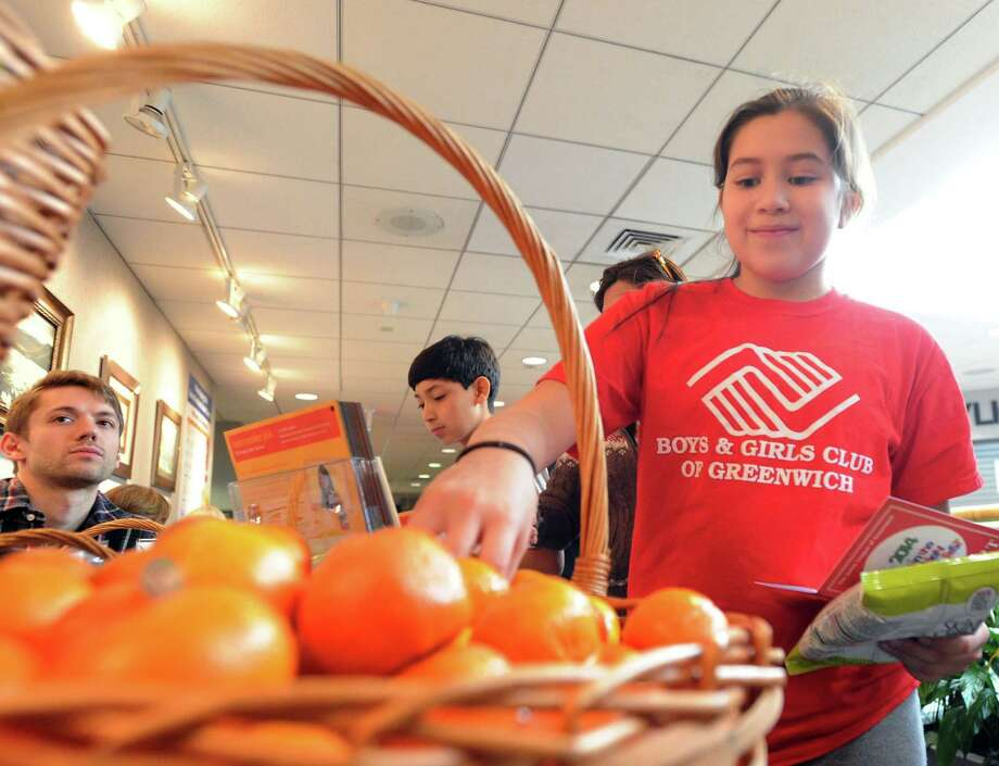 At right, Alyssa Nova, 11, of Greenwich, grabs a tangerine as a snack during the Kids in the Kitchen Fit & Fun Fest at the YWCA of Greenwich, Saturday afternoon, Feb. 1, 2014. The event was sponsored by the Junior League of Greenwich to promote children's health. Photo: Bob Luckey / Greenwich Time