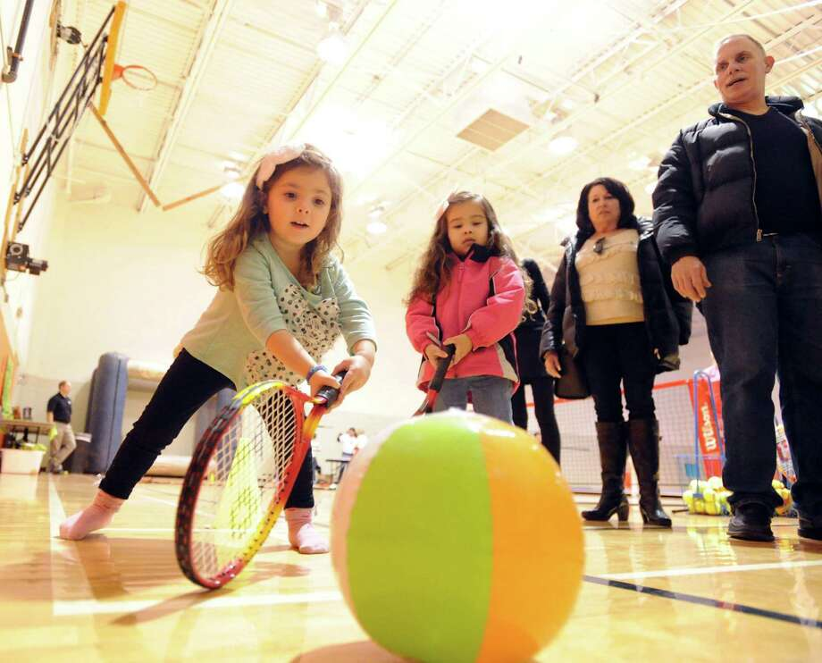 At left, Alexa Fields, 4, of Greenwich, hits a beach ball with a tennis racket during the Kids in the Kitchen Fit & Fun Fest at the YWCA of Greenwich, Saturday afternoon, Feb. 1, 2014.The event was sponsored by the Junior League of Greenwich to promote children's health. Photo: Bob Luckey / Greenwich Time