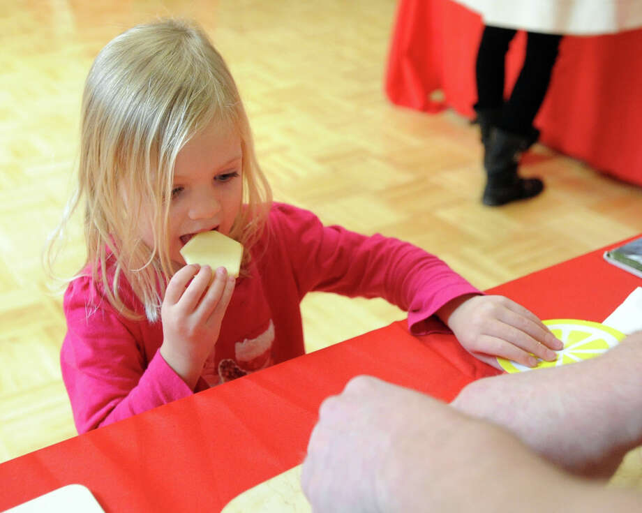 Annie Pedlow, 3, of Greenwich, samples a Fuji apple from Mike Geller's Organic Delivery Service during the Kids in the Kitchen Fit & Fun Fest at the YWCA of Greenwich, Saturday afternoon, Feb. 1, 2014. The event was sponsored by the Junior League of Greenwich to promote children's health. Photo: Bob Luckey / Greenwich Time