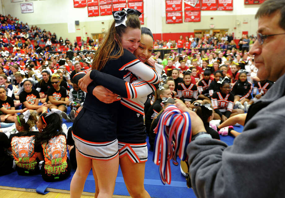 Stamford's Dayna Mynarski, left, and her teammate Chrishma Richards, share a hug after getting their medals, during the 17th Annual 2014 FCIAC Cheerleading Competition at Fairfield Warde High School in Fairfield, Conn. on Saturday February 1, 2014. Photo: Christian Abraham / Connecticut Post