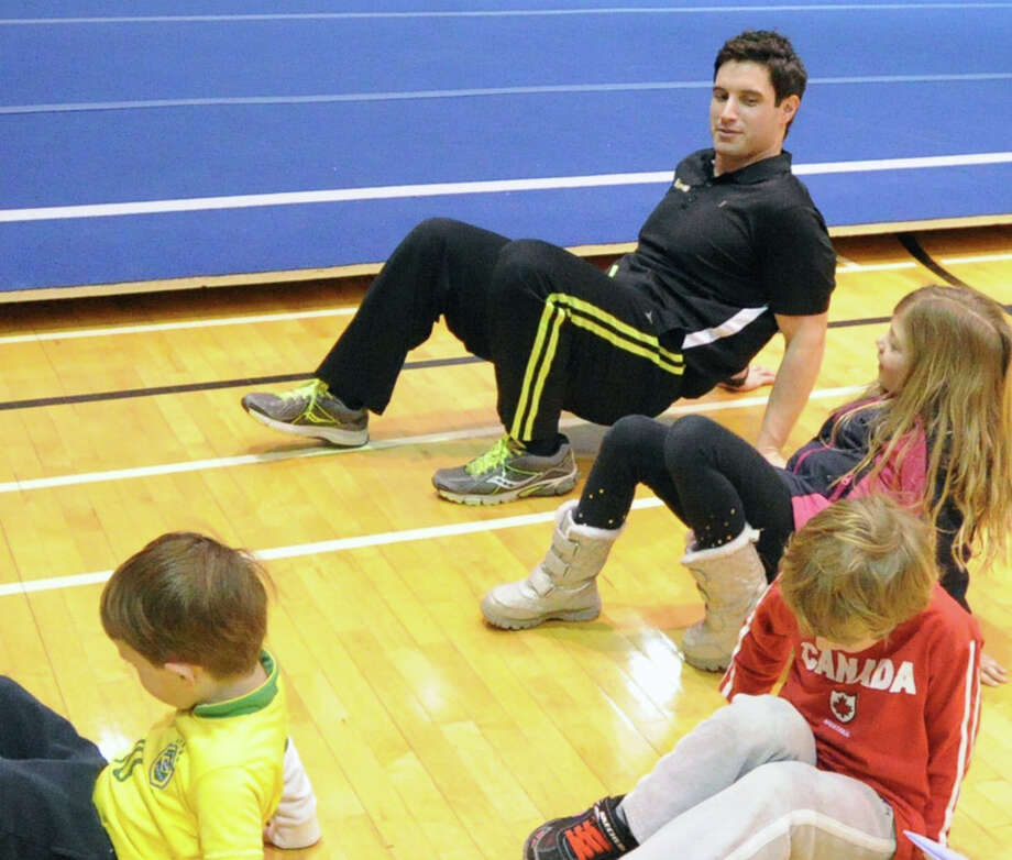 At top, Patrick Jones, fitness instructor, teaches the crab-walk to children during the Kids in the Kitchen Fit & Fun Fest at the YWCA of Greenwich, Saturday afternoon, Feb. 1, 2014. Photo: Bob Luckey / Greenwich Time