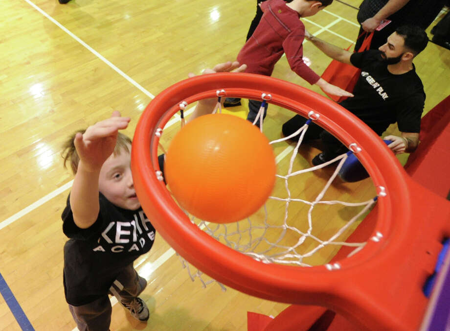Gavin Boucher, 8, of Greenwich, sinks a basket during the Kids in the Kitchen Fit & Fun Fest at the YWCA of Greenwich, Saturday afternoon, Feb. 1, 2014. Photo: Bob Luckey / Greenwich Time