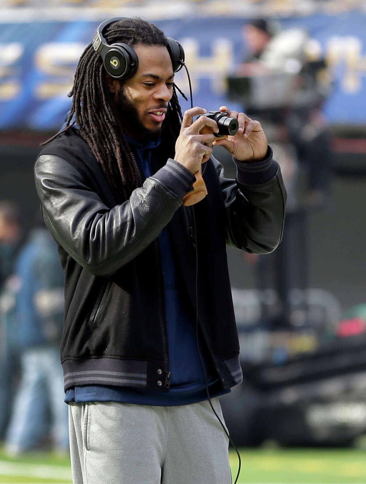 Seattle Seahawks cornerback Richard Sherman takes a photo of the field during a brief visit by the team to MetLife Stadium Saturday, Feb. 1, 2014, in East Rutherford, N.J. The Seahawks and the Denver Broncos are scheduled to play in the Super Bowl XLVIII football game Sunday, Feb. 2, 2014.