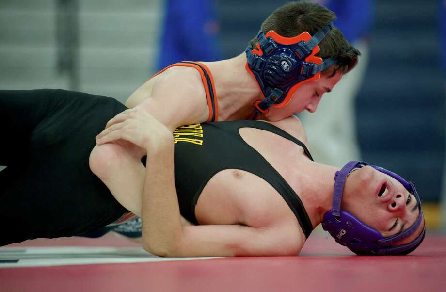 Westhill's Evan Torres, bottom, tries to keep from being pinned by Danbury's Chris Sam during New Fairfield High School's  Duals Tournament, on Saturday, February 1, 2014, in New Fairfield, Conn. They are wrestling in the 106 lb. class. Photo: H John Voorhees III / The News-Times Freelance