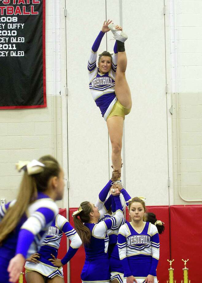 Zoe Carrillo, top, performs with Westhill High School as they compete in the FCIAC cheerleading championships at Fairfield Warde High School in Fairfield, Conn., on Saturday, February 1, 2014. Photo: Lindsay Perry / Stamford Advocate