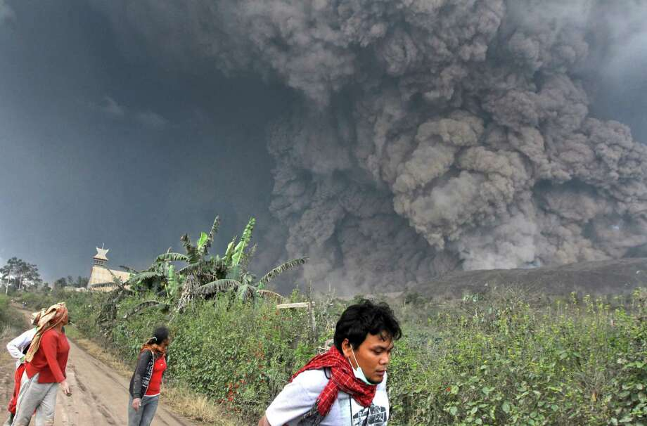 Villagers and a journalist prepare to flee as Mount Sinabung releases pyroclastic flows during an eruption in Namantaran, North Sumatra, Indonesia, Saturday, Feb. 1, 2014. The rumbling volcano in western Indonesia has unleashed fresh clouds of searing gas, killing a number people and injuring fewothers. (AP Photo) Photo: STR / AP
