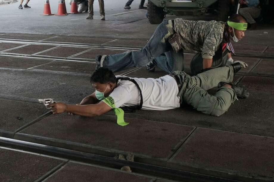 A protester trying to disrupt Sunday's elections takes aim before firing at would-be voters Saturday in the streets of Bangkok. Six people were wounded. Photo: NICOLAS ASFOURI, Staff / AFP