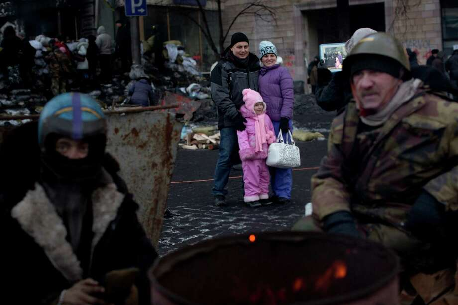 A family is photographed near a barricade as opposition supporters warm themselves around the fire Saturday near Kiev's Independence Square in Ukraine. Photo: Emilio Morenatti, STF / AP