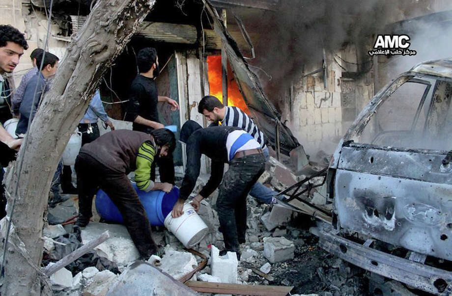 In this citizen journalism image provided by Aleppo Media Center (AMC), an anti-Bashar Assad activist group, and authenticated based on its contents and other AP reporting, Syrian citizens fill water in a bucket to extinguish shops in flames caused by a Syrian government forces warplane attack, at al-Bab neighborhood in Aleppo, Syria, Saturday, Feb. 1, 2014. Syrian military helicopters dropped barrels packed with explosives on rebel-held areas of the northern city of Aleppo on Saturday, killing at least a dozen of people including a family trapped in a car, as government forces inched closer to opposition-held areas. (AP Photo/Aleppo Media Center, AMC) Photo: HOEP / Aleppo Media Center AMC