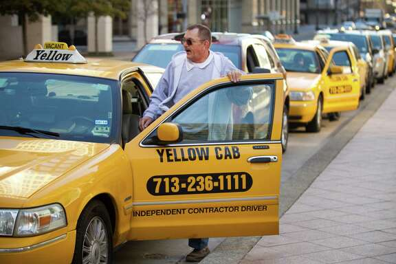 Taxi driver Chuck Peto gets in his car while waiting for a fare at a cab stand on Milam downtown.