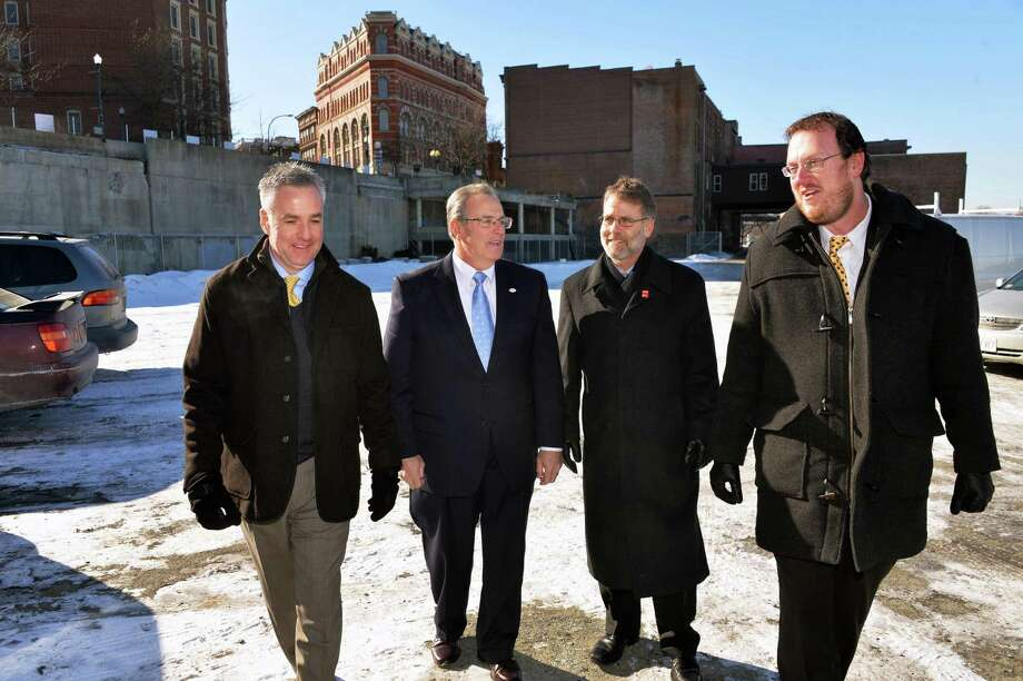 Greg Burns of Kirchhoff Consigli, left, Troy Mayor Lou Rosamilia, Randy Collins of CSArch and Jeff Buell of Sequence Development, right, discuss the Monument Square redevelopment project Thursday, Jan. 30, 2014, at the Monument Square site in Troy, N.Y.  (John Carl D'Annibale / Times Union) Photo: John Carl D'Annibale / 00025567A