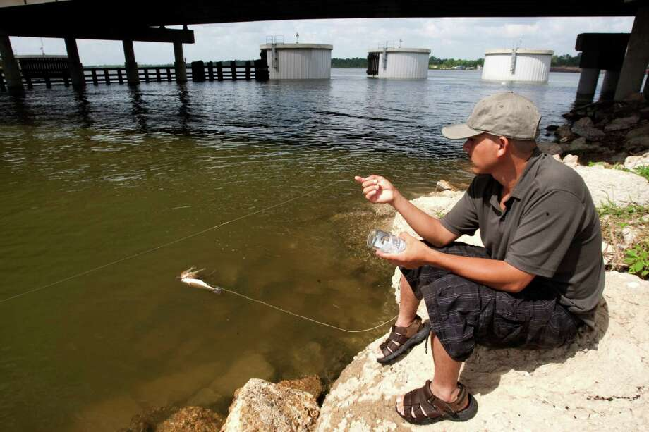 Despite warning signs, Giovani Pimale is among those undeterred from fishing in San Jacinto River. Photo: Brett Coomer, Staff / Houston Chronicle