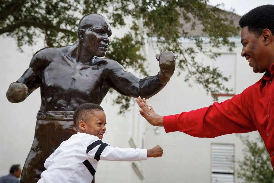 "Spencer Collins, 4, boxes with his father Sam in front of a statue of Jack Johnson during the dedication ceremony of a historical marker honoring Johnson, the first black world heavyweight champion, at Jack Johnson Park, Saturday, Feb. 1, 2014, in Galveston.  The monument is the first state recognition of the boxer, whose victory over a white opponent gave rise to the search by racists for ""the Great White Hope"" to defeat the black champion. Photo: Michael Paulsen, Houston Chronicle / © 2014 Houston Chronicle"
