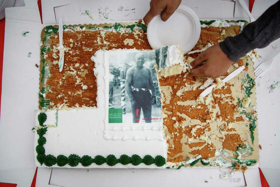 A cake is cut into slices during the dedication ceremony of a historical marker honoring Jack Johnson, the first black world heavyweight champion, at Jack Johnson Park, Saturday, Feb. 1, 2014, in Galveston. Photo: Michael Paulsen, Houston Chronicle / © 2014 Houston Chronicle