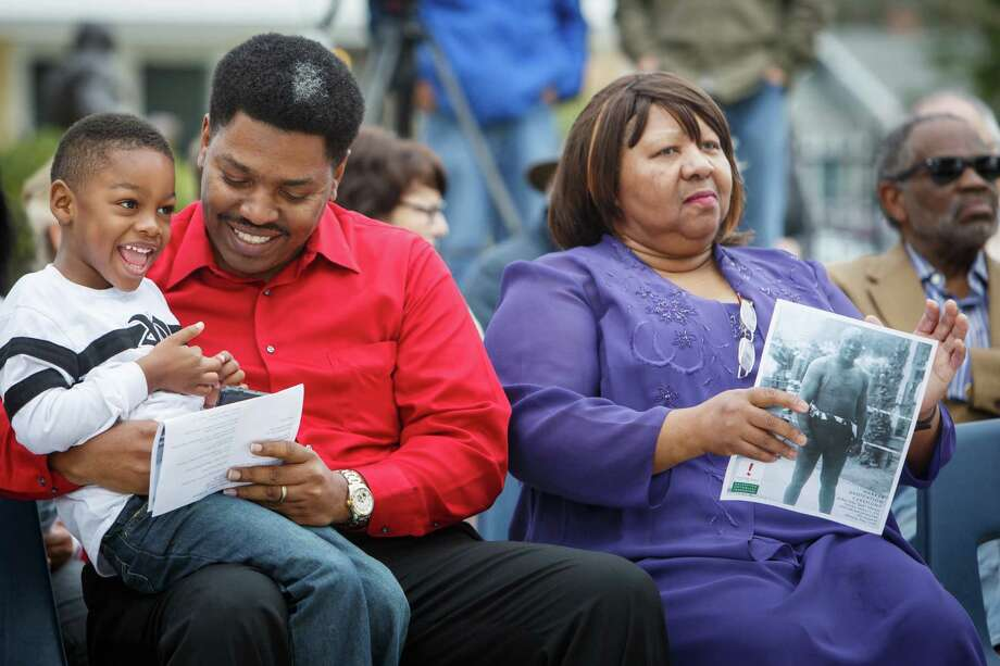 Sam Collins, center, holds his son Spencer, 4, as they sit next to Linda Haywood, the great-great niece of Jack Johnson, during the dedication ceremony of a historical marker honoring Jack Johnson, the first black world heavyweight champion, at Jack Johnson Park, Saturday, Feb. 1, 2014, in Galveston. Photo: Michael Paulsen, Houston Chronicle / © 2014 Houston Chronicle