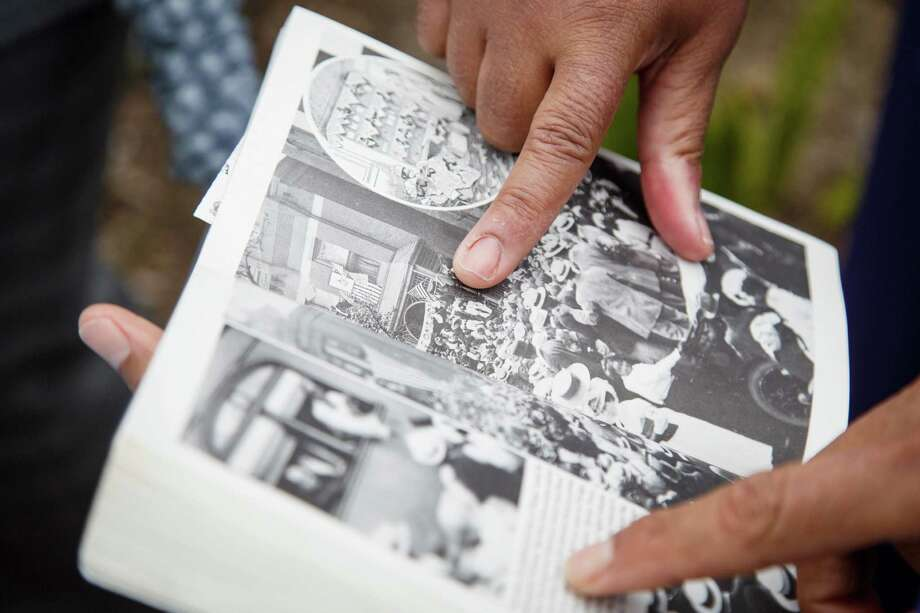 Linda Haywood, the great-great niece of Jack Johnson, points to a family photo in a book held by Andy Lopez during the dedication ceremony of a historical marker honoring Jack Johnson. Photo: Michael Paulsen, Houston Chronicle / © 2014 Houston Chronicle