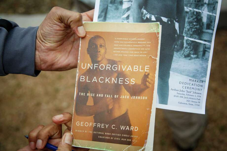 Andy Lopez holds a book on Jack Johnson during the dedication ceremony of a historical marker honoring Johnson. Photo: Michael Paulsen, Houston Chronicle / © 2014 Houston Chronicle