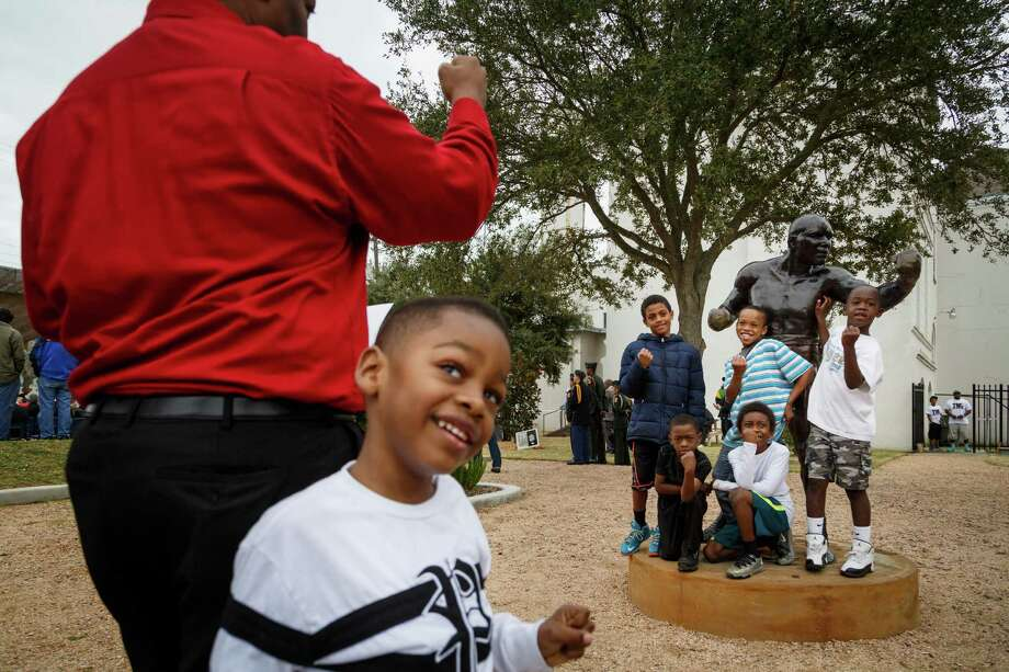 Spencer Collins, 4, center, looks back as his father Sam, left, takes a photo of Daiveion Tillman, 8, left to right standing, Deryus Phillips, 10, Kourtney Archie, 7, Michael Gray, 6, kneeling left, and Josh Arthur, 6, kneeling right, in front of a statue of Jack Johnson, during the dedication ceremony of a historical marker honoring Johnson. Photo: Michael Paulsen, Houston Chronicle / © 2014 Houston Chronicle