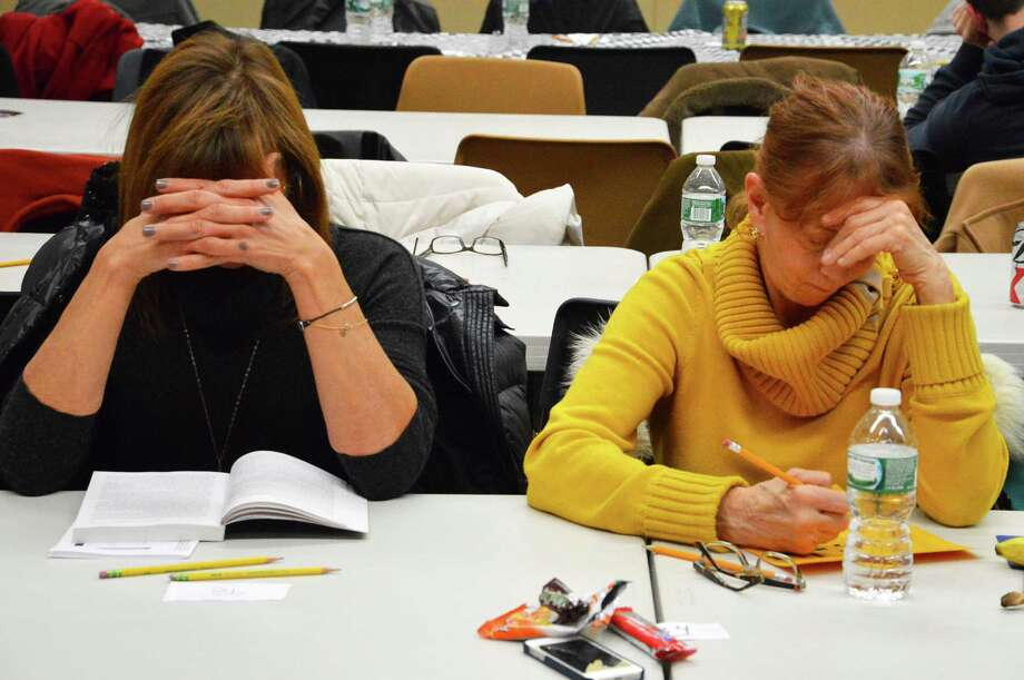 Joyce Eldh, left, and Lynn Whitton, both of Westport, concentrate on their puzzles Saturday at the 15th annual Crossword Puzzle Contest sponsored by the Westport Library. Photo: Jarret Liotta / Westport News contributed