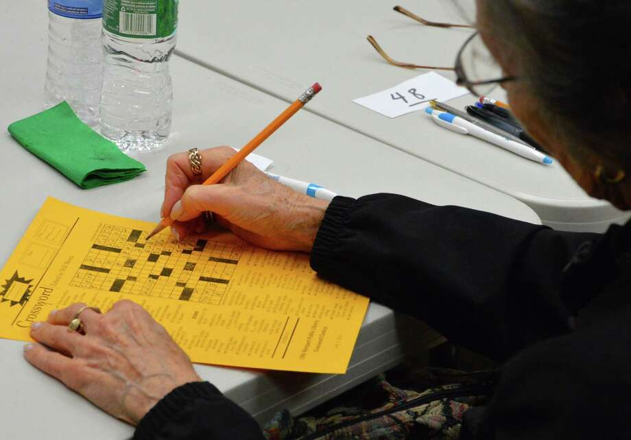 Zita Casey of Westport works on a puzzle in the crosswords contest Saturday at the Westport Library. Photo: Jarret Liotta / Westport News contributed