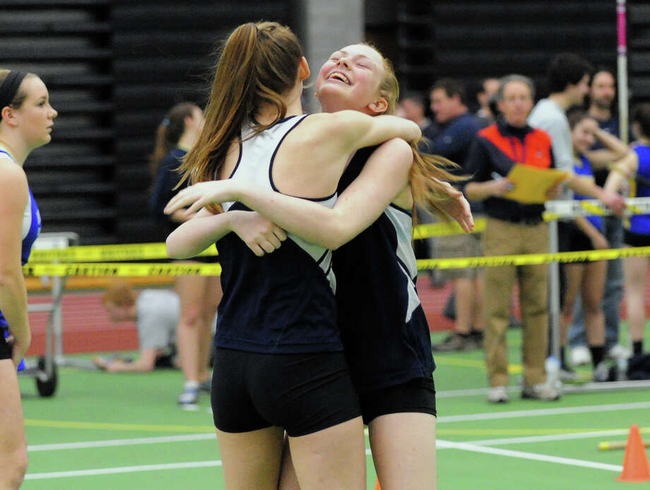 Weston's Leila Stugis, facing camera, gets a hug from teammate Chloe Shapiro, after competing in the high jump, during SWC Chapionship track action at Hillhouse High Scholl in New Haven, Conn. on Saturday February 1, 2014. Photo: Christian Abraham / Connecticut Post