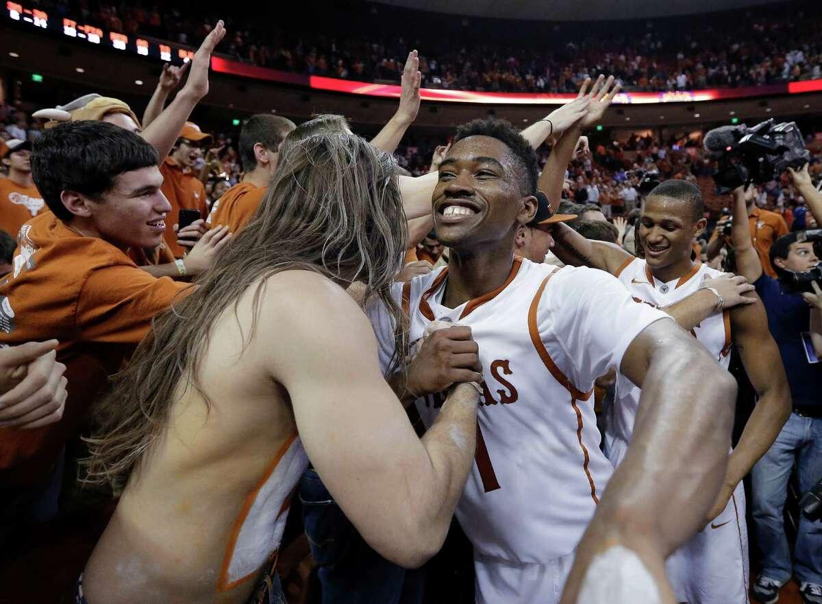Texas' Isaiah Taylor (1) celebrates with fans after an NCAA college basketball game against Kansas, Saturday, Feb. 1, 2014, in Austin, Texas. Texas won 81-69. (AP Photo/Eric Gay)