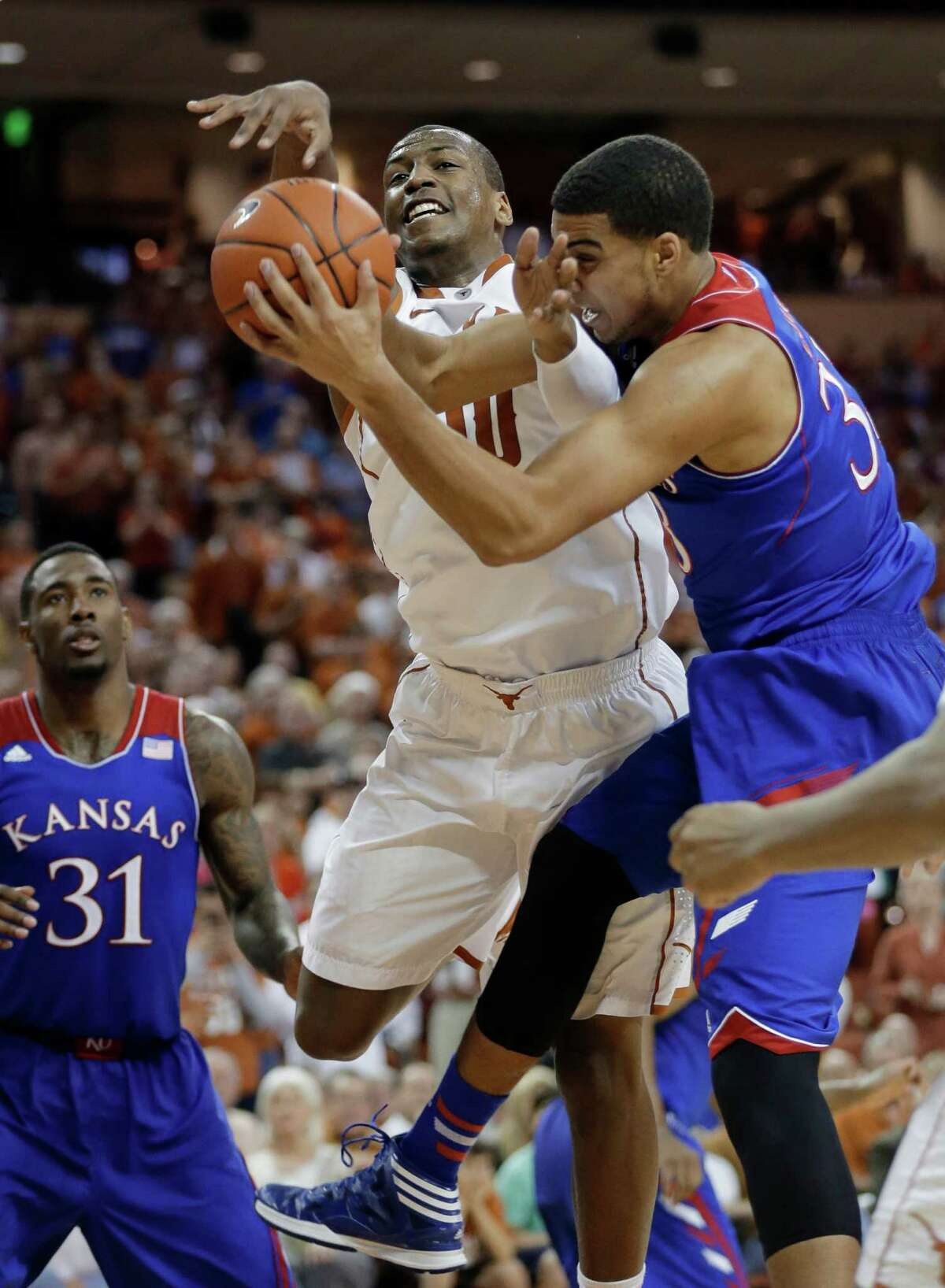 Texas' Jonathan Holmes (10) and Kansas' Landen Lucas, right, scramble for a rebound during the first half of an NCAA college basketball game, Saturday, Feb. 1, 2014, in Austin, Texas. (AP Photo/Eric Gay)